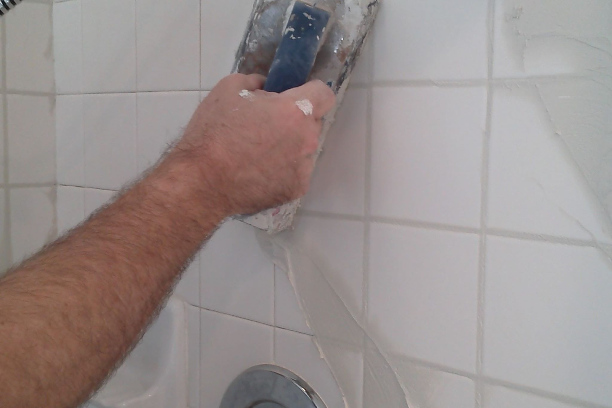 Removing old grout and installing new grout and caulk